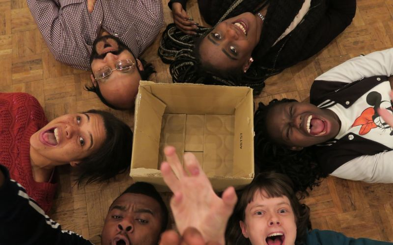 Six people lying in a circle, surrounding a cardboard box