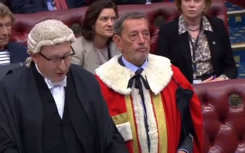 Two men, one with a lawyer's wig, and the other wearing a red, fur-trimmed robe, in the House of Lords