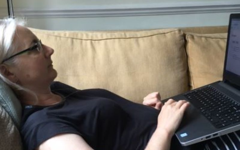 Catherine Hale lies on a sofa as she works on her laptop