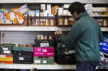A man sorts shelves stacked with packets and tins of food