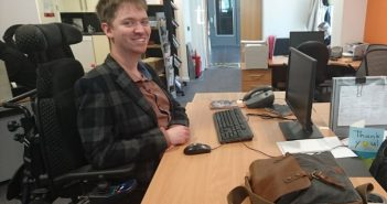 A young wheelchair-user sits smiling at an office desk