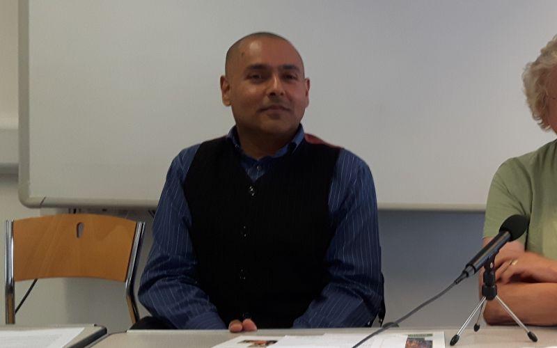 Kamran Mallick sitting behind a table