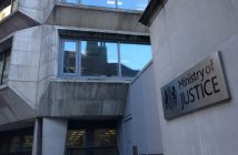 Ministry of Justice sign on the wall of a building, overlooked by windows