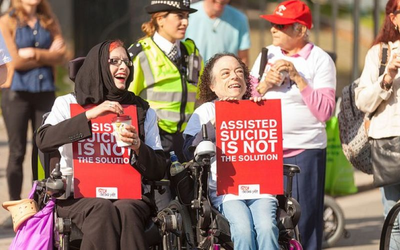 Two female wheelchair-users hold placards saying 'assisted suicide is not the solution'