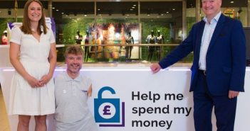 Two men and a woman beside a poster which says 'help me spend my money'