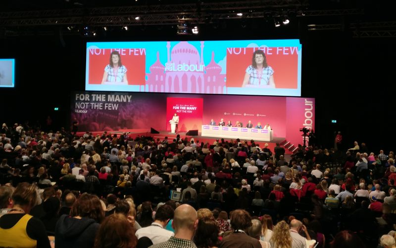 Delegates at the Labour conference listen to a speaker on the platform