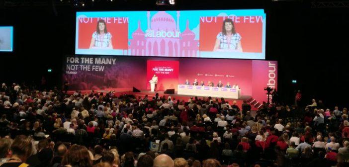 Delegates at the Labour conference listen to a speaker on the platform