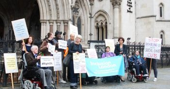 Campaigners from Inclusion London with placards outside the Royal Courts of Justice