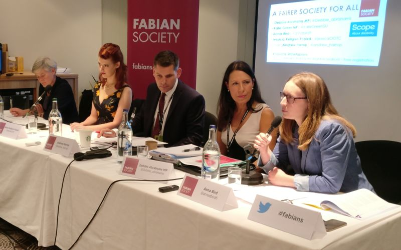 Debbie Abrahams and two other panellists listen to a woman speaking
