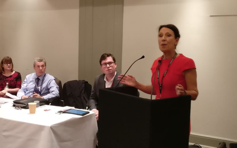 Debbie Abrahams speaking at a podium watched by panel members