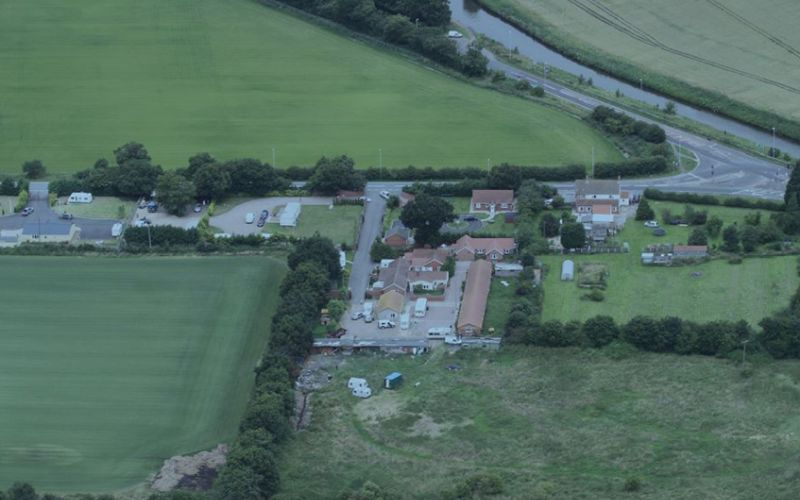 An aerial view of a farm with outbuildings, fields and caravans