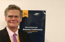 Stephen Lloyd in front of a sign for the Liberal Democrat conference
