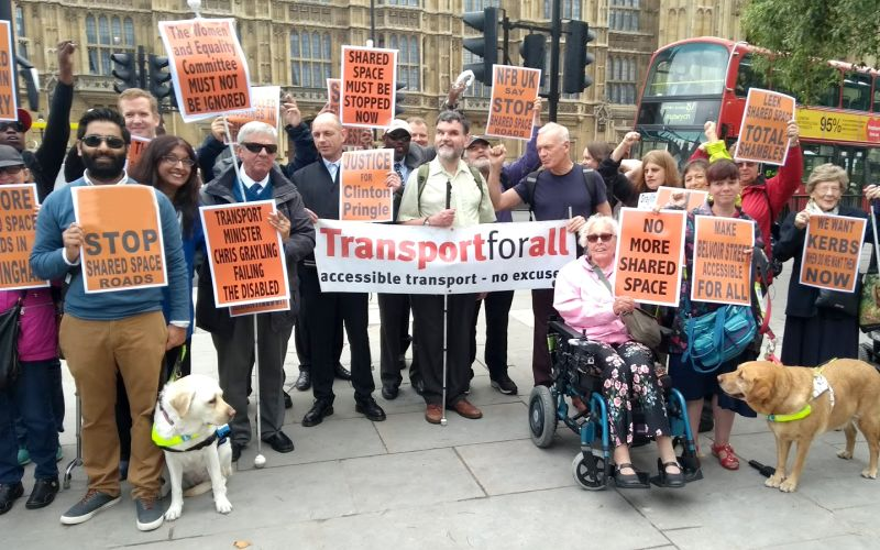 Campaigners with shared space placards and guide dogs outside parliament