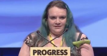 Fiona Robertson speaking to the SNP conference above a sign saying 'Progress'
