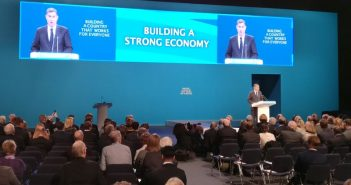 David Gauke speaking to the party conference, with his picture on the screen behind him
