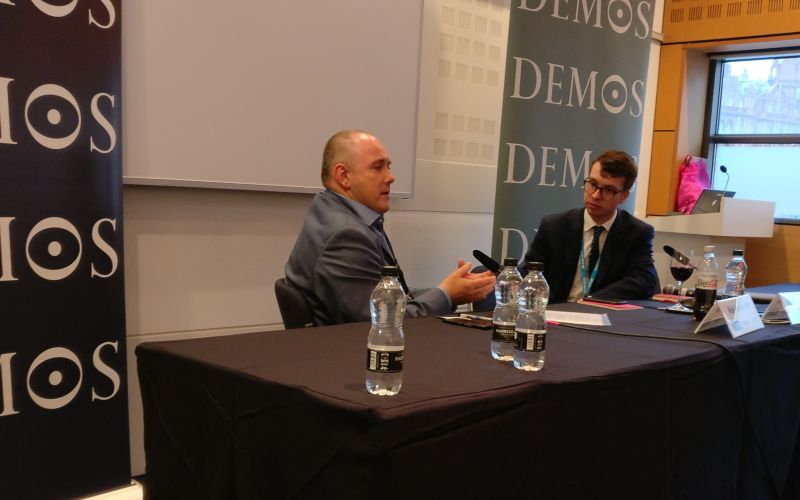 Robert Halfon talking to Sebastian Payne behind a table