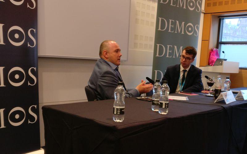 Robert Halfon talking to Sebastian Payne behind a table