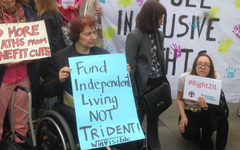 Claire Glasman at a protest, holding a WinVisible sign calling for independent living not Trident