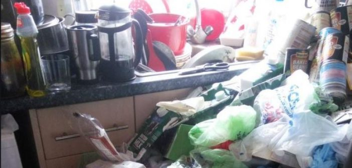 Bags of rubbish piled up in front of a kitchen sink