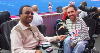 Martyn Sibley and Srin Madipalli in their wheelchairs in the crowd beside a hockey match