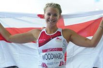 Bethany Woodward, smiling, wearing athletics kit and holding an England flag behind her head