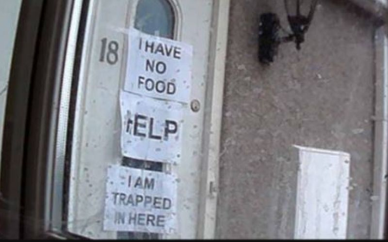 Signs taped to a front door saying Help, I Have No Food, and I Am Trapped In Here