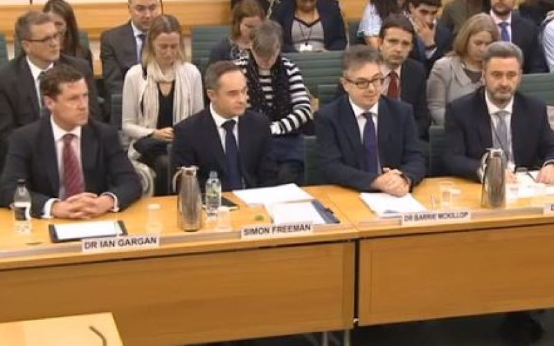 Four executives from Capita and Atos sit behind a table, with other people sat behind them