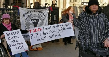 Protesters at the vigil, holding banners about PIP, in front of the Royal Courts of Justice