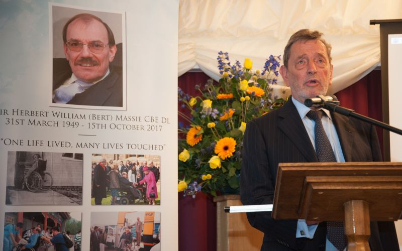 Lord Blunkett speaking at a podium in front of pictures of Sir Bert Massie