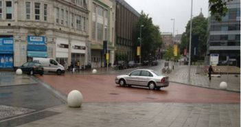 Cars crossing a flat space, with bollards and surrounding buildings