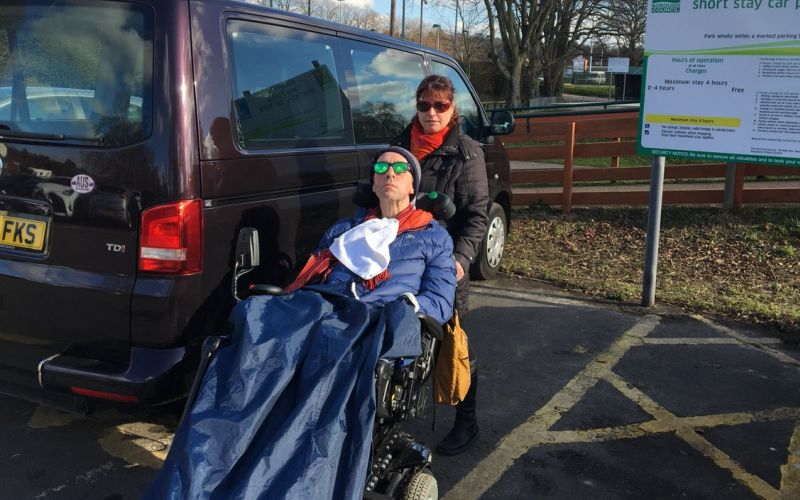 Andrew Knowlman in his wheelchair in front of a van with a woman behind him