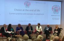 Seven people on a stage, with Juliet Marlow in a wheelchair far right, in front of a screen that says Choice at the end of life