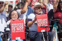Liz Carr holds up a sign saying Assisted suicide is not the solution, next to a man holding a sign saying don't give doctors a licence to kill, in front of other protesters