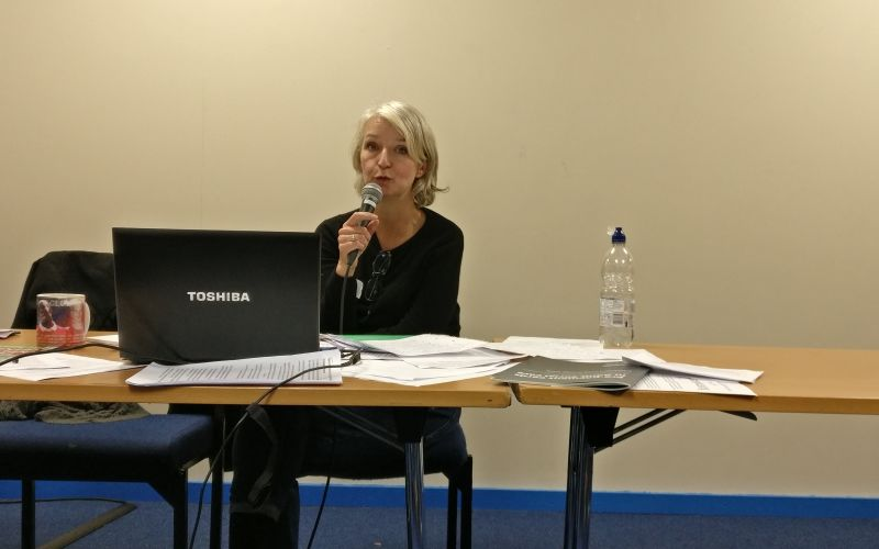 Tracey Lazard sitting behind a table and holding a microphone