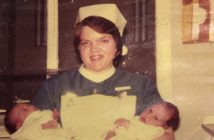 Anne Savidge, in a midwife's uniform, holding two babies, in a fading photograph