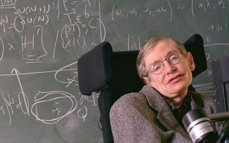Stephen Hawking in front of a blackboard covered in mathematical symbols