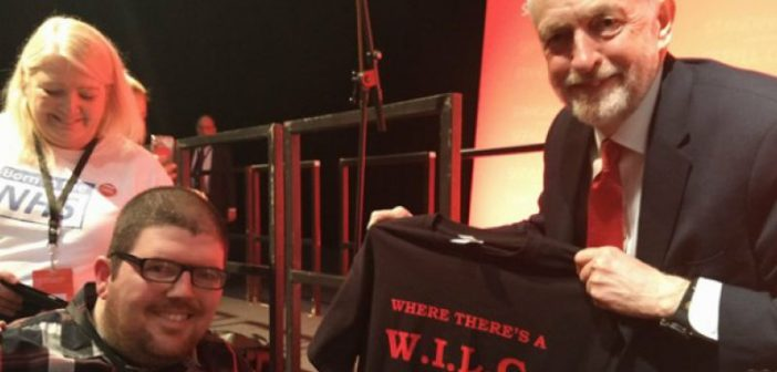 Nathan Lee Davies smiling as Jeremy Corbyn, also smiling, holds up one of the tee shirts