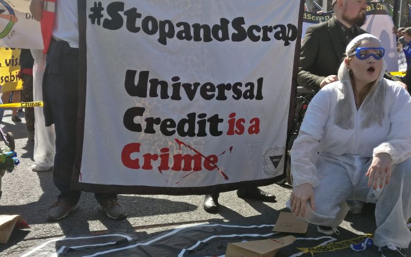 A woman dressed as a crime scene investigator in front of a poster saying universal credit is a crime