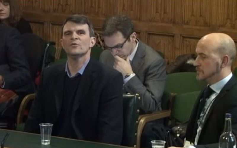 Robin Christopherson giving evidence in parliamennt, watched by another man