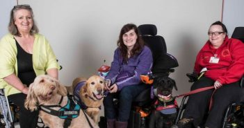 Three women, sitting in their wheelchairs, with their assistance dogs