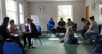 Young people sitting in discussion groups in a room