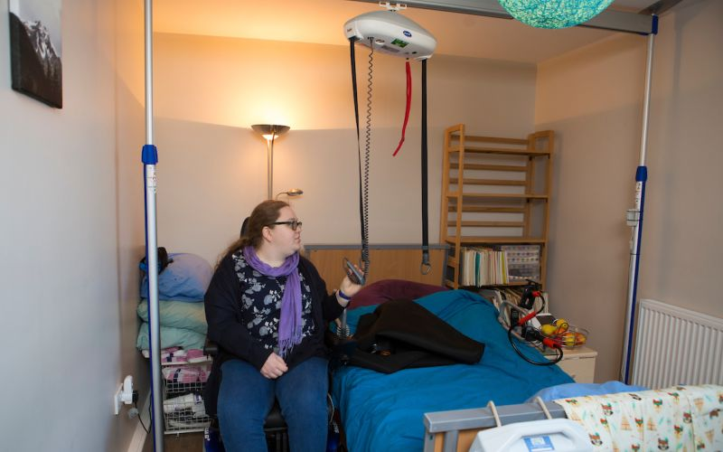 A woman using a hoist in her bedroom