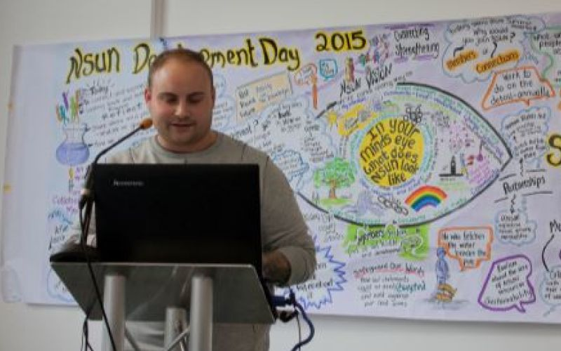 A man speaks to a conference in front of a detailed picture diagram