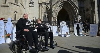 Two women in wheelchairs in front of a series of white gravestones erected outside the Royal Courts of Justice