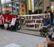 Protesters outside a building with a banner saying UK disability rights abused by UK