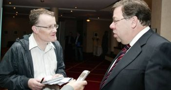 Declan McSweeney holding a notebook and pen, talking to Brian Cowen