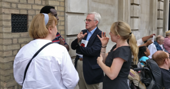 John McDonnell talking to a man and two women, one of whom is signing