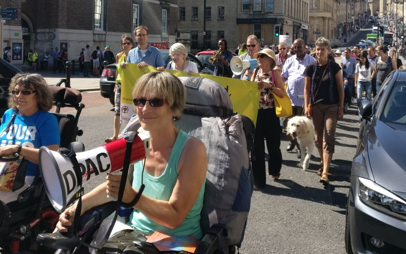 A wheelchair-user holds a megaphone at the front of a group of people marching along a road