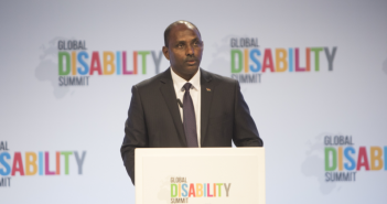 Ukur Yatani Kanacho speaking at a podium at the Global Disability Summit