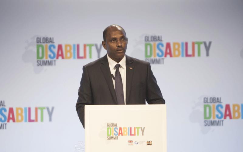 Ukur Yatani Kanacho speaking at a podium at the Global Disability Summit